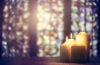 Photo of candles in front of stained glass windows