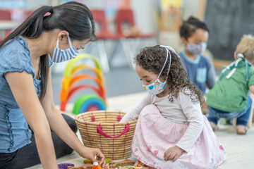 Photo of a caregiver and little girl playing at a daycare while wearing masks