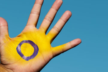 Photo of a hand painted to depict the intersex flag with yellow and a purple circle