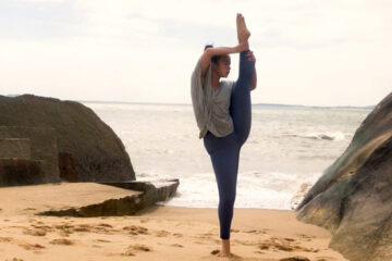 Photo of a single dancer with toes pointed up on the beach