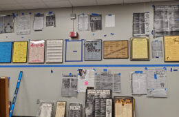 Photo of Film Society posters being planned out on a wall to be hung in Strosacker Auditorium