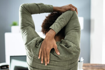 Photo of a bussinessperson stretching at their desk