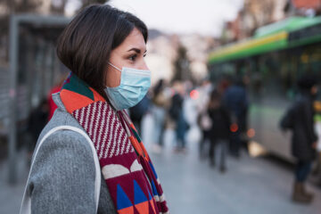 Woman wearing facemask waits for bus