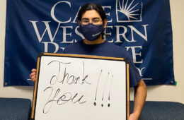 "Photo of a student wearing a mask and holding a board that says ""thank you"" and standing in front of a CWRU flag"