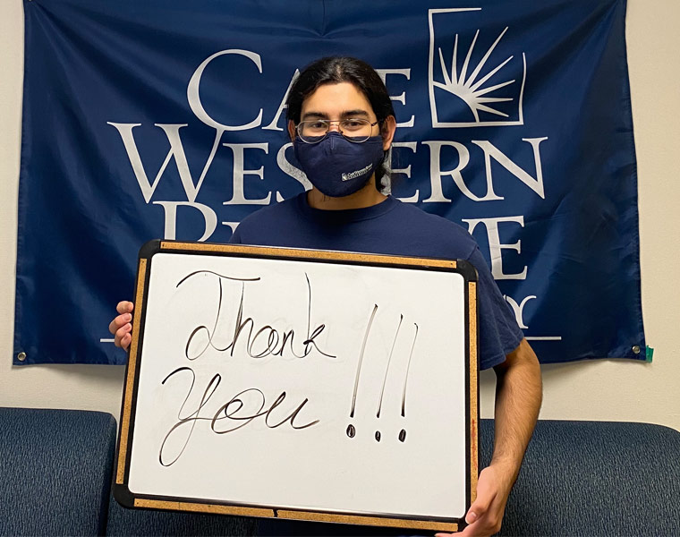 """Photo of a student wearing a mask and holding a board that says """"thank you"""" and standing in front of a CWRU flag"""