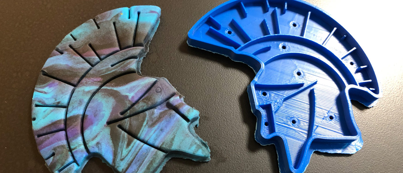 Photo of a cookie cutter of CWRU's Spartan next to dough cut with it