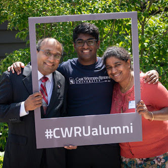 """Photo of a family of three posing for a photo with a frame that says """"#CWRUalumni"""""""