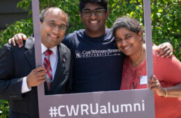 "Photo of a family of three posing for a photo with a frame that says ""#CWRUalumni"""