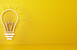 Photo illustration of a lightbulb against a bright yellow background representing the concept of an idea