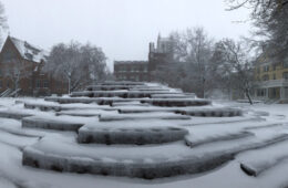 Photo of snow blanketing the Merging sculpture with a snowy Mather Quad behind it