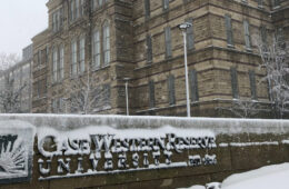 Photo of CWRU signage covered in snow with Adelbert Hall in the background