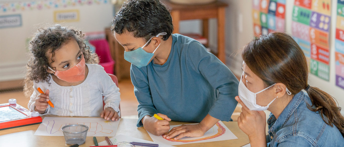 Photo of two children wearing masks and coloring while a child care worker watches them