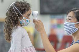 Photo of a child care worker wearing a mask while taking the temperature of a child wearing a mask