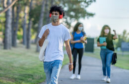 College students wearing masks walking on campus