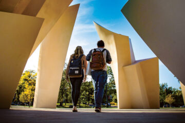 Photo of two students walking through the Turning Point statue on CWRU campus