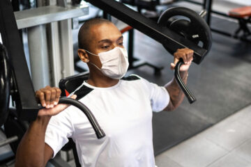 Photo of a man wearing a mask while using a weight lifting machine