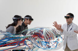 Photo of students wearing HoloLens devices gathered around a 3D model of the body in an augmented reality setting