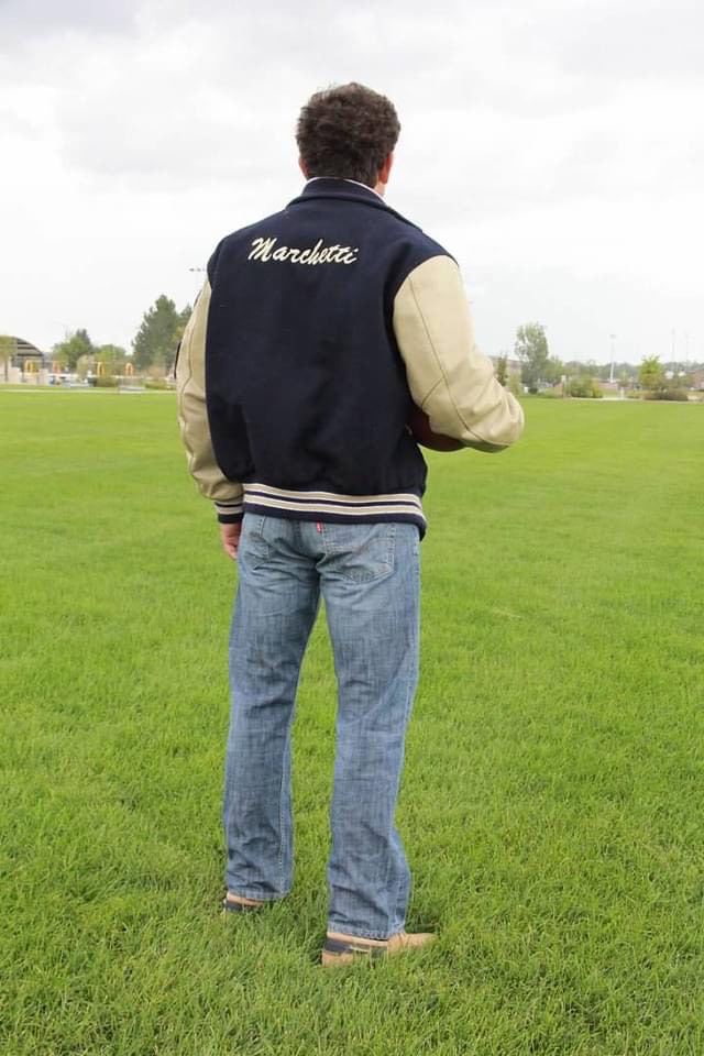 Photo of Garrett Marchetti from behind wearing a varsity jacket with his last name on it