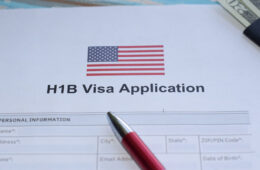 "Photo of a paper that says ""H1B visa application"" and a pen"