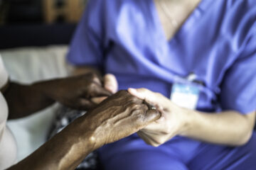 Photo of a health care provider hold an elderly patient's hands for comfort.