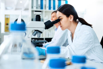 Photo of a female researcher looking into a microscope
