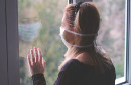 Photo of a masked woman looking out a window
