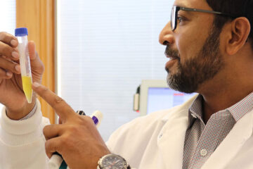 Photograph of researcher Anirban Sen Gupta pointing at a vial