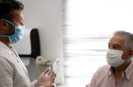 Photo of a man talking to a doctor, both wearing masks
