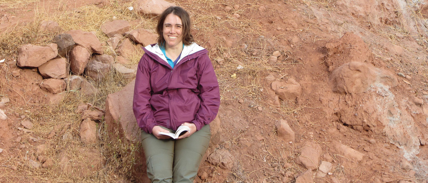 Photo of Beverly Saylor sitting in a rocky environment with a book in her hands