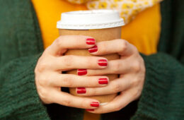 Close-up photo on the hands of a woman holding a to-go coffee cup