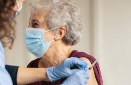 Photo of an elderly woman receiving a vaccine